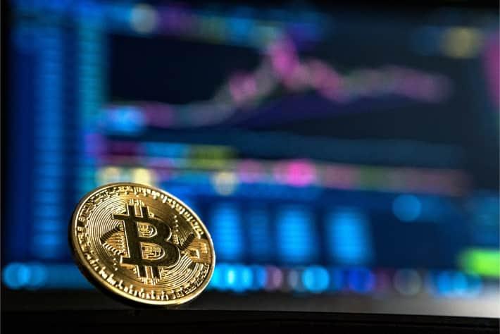 在笔记本电脑屏幕前的比特币代表WannaCry勒索软件攻击所需的赎金