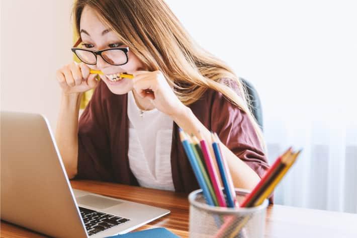 女人在笔记本电脑旁沮丧地咬铅笔
