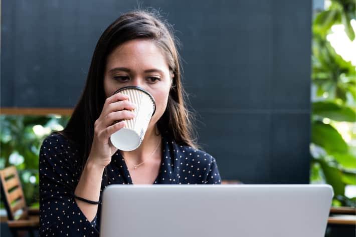 女人在笔记本上浏览,喝咖啡